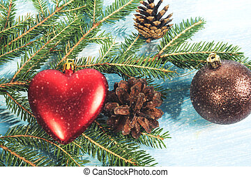Christmas tree branch on wooden background with heart, Christmas ball and pine cones
