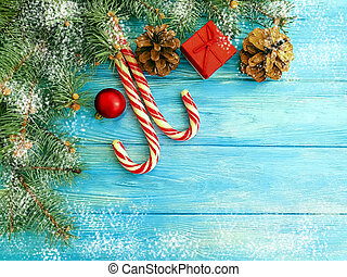 Christmas tree branch, pinecone, candy on a blue wooden background frame