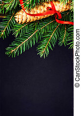 Christmas Tree Branch with cone and red ribbon on Black board wi