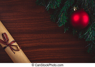 Christmas tree branch with red ball, a letter with a ribbon on the table flat lay top view copy space