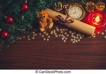 Christmas tree branch with red balls, a candle, a letter with a ribbon, a bear toy, a cone on the table flat lay top view copy space