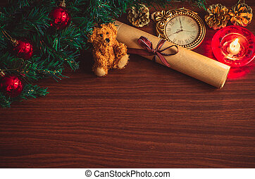 Christmas tree branch with red balls, a candle, a letter with a ribbon, a bear toy on the table flat lay top view copy space