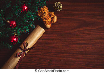 Christmas tree branch with red balls, a letter with a ribbon, a bear toy on the table flat lay top view copy space