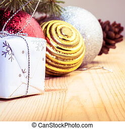 Christmas tree branches with cones, decorations and gift box on the left side of the image with pine wooden board
