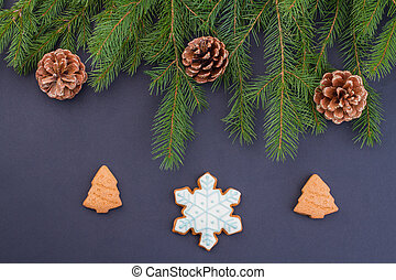 Christmas tree branches with pine cones and cookies.