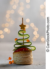 Christmas tree canape with cucumber slice, salmon pate and red caviar
