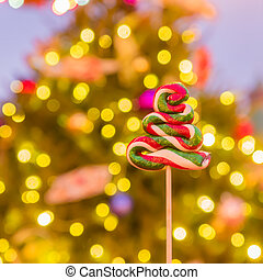 Christmas tree candy on festive bokeh background.