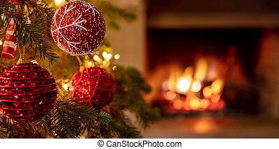 Christmas tree close up on blurred burning fireplace background