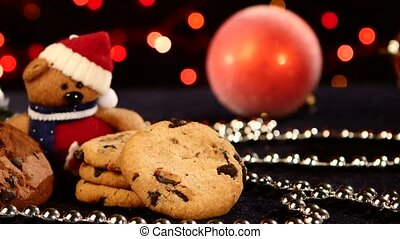 Christmas tree, cookies with decoration, pine cone on black, beads, bokeh, light, garland, cam oves to the left