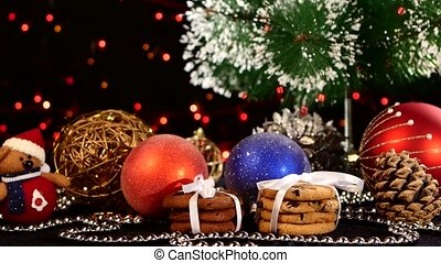 Christmas tree, cookies with decoration, pine cone on black, bokeh, light, garland, cam oves to the right