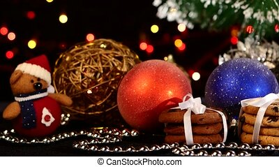 Christmas tree, cookies with decoration, pine cone on black, bokeh, light, garland, cam oves to the right, close up
