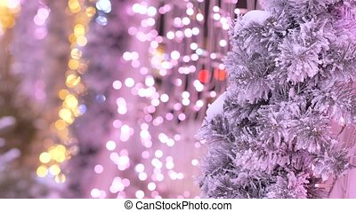 Christmas tree covered with snow. In the background are colored garlands. Out of focus.