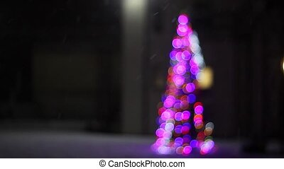 Christmas tree decorated with colored lights stands in the...