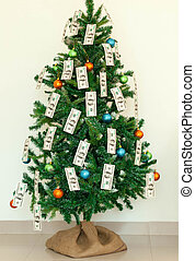 Christmas tree decorated with dollars notes.