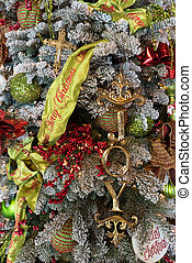 Christmas tree decorated with Merry Christmas garland and the word joy