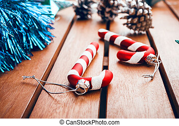 Christmas tree decorations in the form of candy cane on wooden table