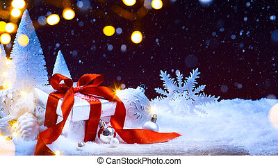 Christmas tree light; festive background with Christmas balls and gift box on snow
