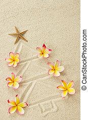 Christmas tree made of sand and frangipani flowers. Xmas beach holiday concept