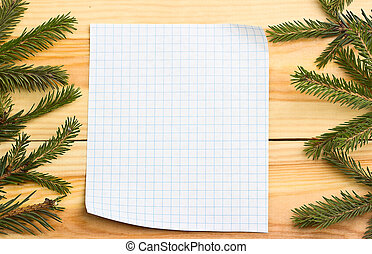 Christmas tree on a wooden background with white leaf