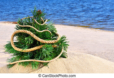 Christmas tree on the beach against blue ocean
