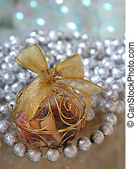 Christmas Tree Ornament Gold Filigree - A gold Christmas ornament filled with potpourri with a huge gold bow on top sits on a glass table.