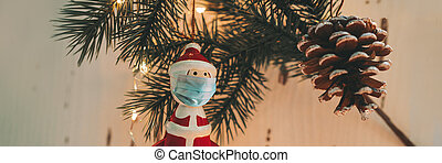 Christmas tree santa claus ornament wearing surgical face mask for coronavirus prevention during holiday family gathering. Banner of social distancing