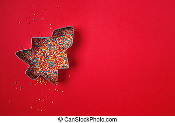 Christmas tree shape cookie cutter filled with colorful sugar sprinkles