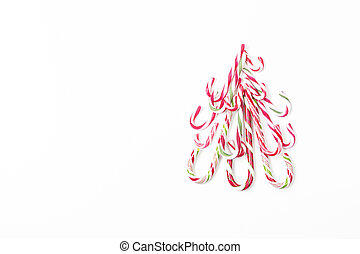 Christmas tree shape made of candy canes on white background. Top view