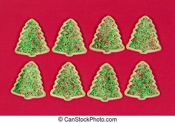 Christmas tree shaped cookies on red background
