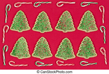 Christmas tree shaped cookies surrounded by candy cane border on red background