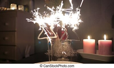 Christmas tree shaped sparkles with two glasses of champagne and candles