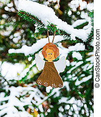 Christmas tree toy in the form of an angel hangs on a snow-covered fir branch in the forest. New Year and Christmas concept