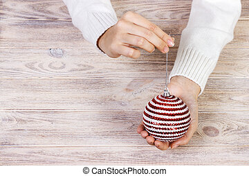 Christmas tree toy in the hands of a women. New Year. Christmas. Wooden Background