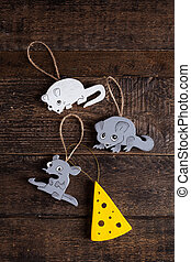 Christmas tree toys lie on a brown table. Two gray and white mice and a piece of cheese