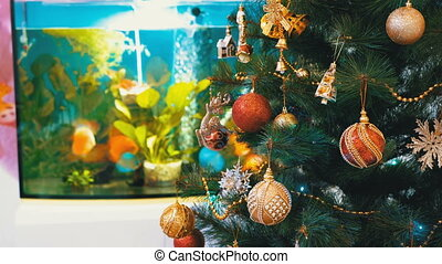 Christmas Tree with Balls, Decorations and a Garland in front of the Aquarium Inside the Room