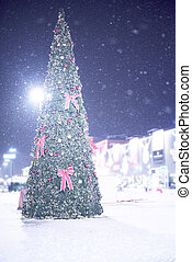 Christmas tree with bows, garlands and balloons in snow at night on the square