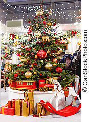 Christmas tree with colorful decorative balls. New Year decorations and gifts - rocking horse, presents ni red and gold wrapping paper. Festive interior of a shop.