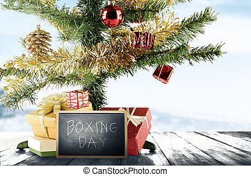 Christmas tree with gift box and Boxing Day text on the blackboard on wooden floor
