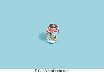 Christmas tree with snow in a glass jar on blue winter background. Minimal New Year concept
