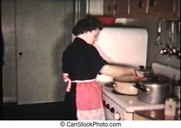 Two women work hard to prepare a lovely Turkey dinner for the big Christmas meal. (SCANNED FROM 8mm FILM)