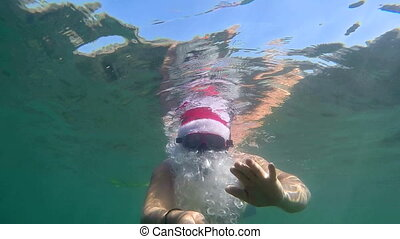 Christmas vacation Santa Claus snorkeling underwater with...