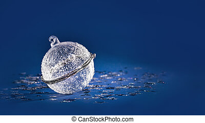 Christmas white crystal bauble on blue glitter background