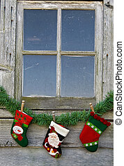 Christmas Window - Holiday stockings hanging under an old...