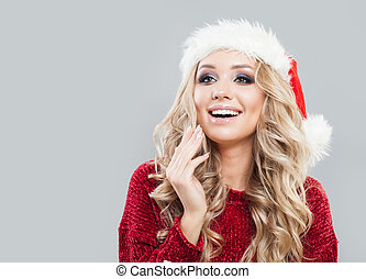 Christmas, winter, happiness concept - smiling woman in santa hat on background with copy space