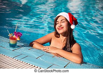 christmas woman beautiful smiling in Santa's hat with a cocktail in the pool in Egypt
