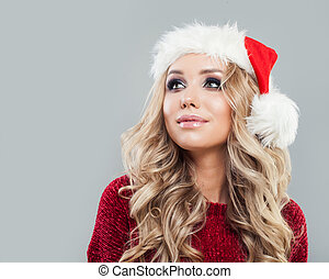Christmas woman in santa hat looking up on background with copy space