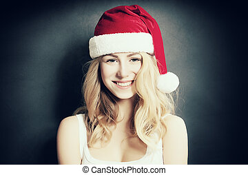 Christmas Woman laugh. Beautiful Xmas Fashion Model in Santa Hat on Blue Background