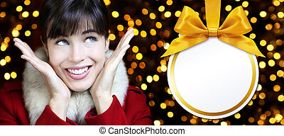 Christmas women with ball in golden lights background