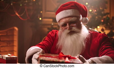 Christmas wonder at night, kind Santa Claus is giving gift, portrait of kind old wizard in living room, Xmas mystery and fairy tale