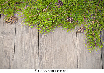 Christmas wooden background with fir branches and pine cones